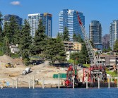 Meydenbauer Bay Park with crane on barge and heavy equipment along shoreline, City of Bellevue buildings skyscape