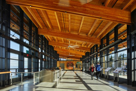 timber beams and ceiling with large windows and two people walking inside terminal building, one in blue and one in red shirt