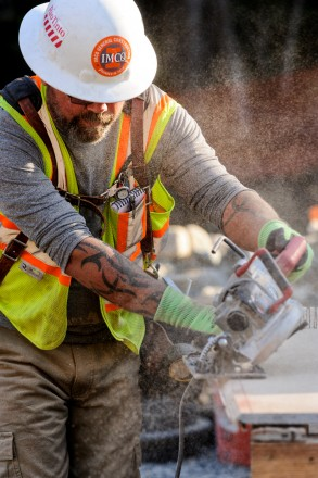 Construction worker in hard hat operating a saw