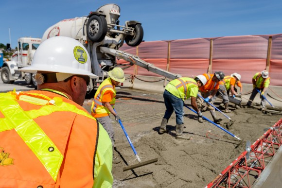 Construction workers in hard hats and high visibility vests working on I-90 roadway to place concrete during a closure, with blue sky in background