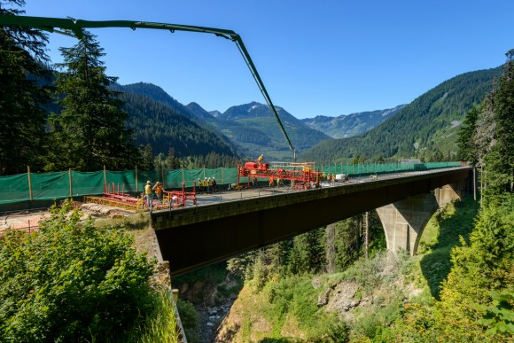 Construction crew performing a bridge deck pour at heights in North Bend with forest background