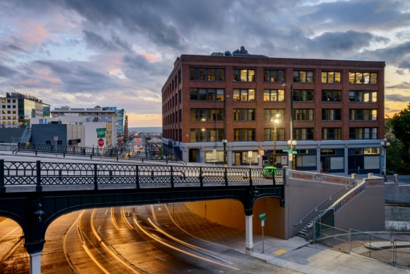 Yesler bridge and Seattle roadway with cloudy sunset sky and brick building in background