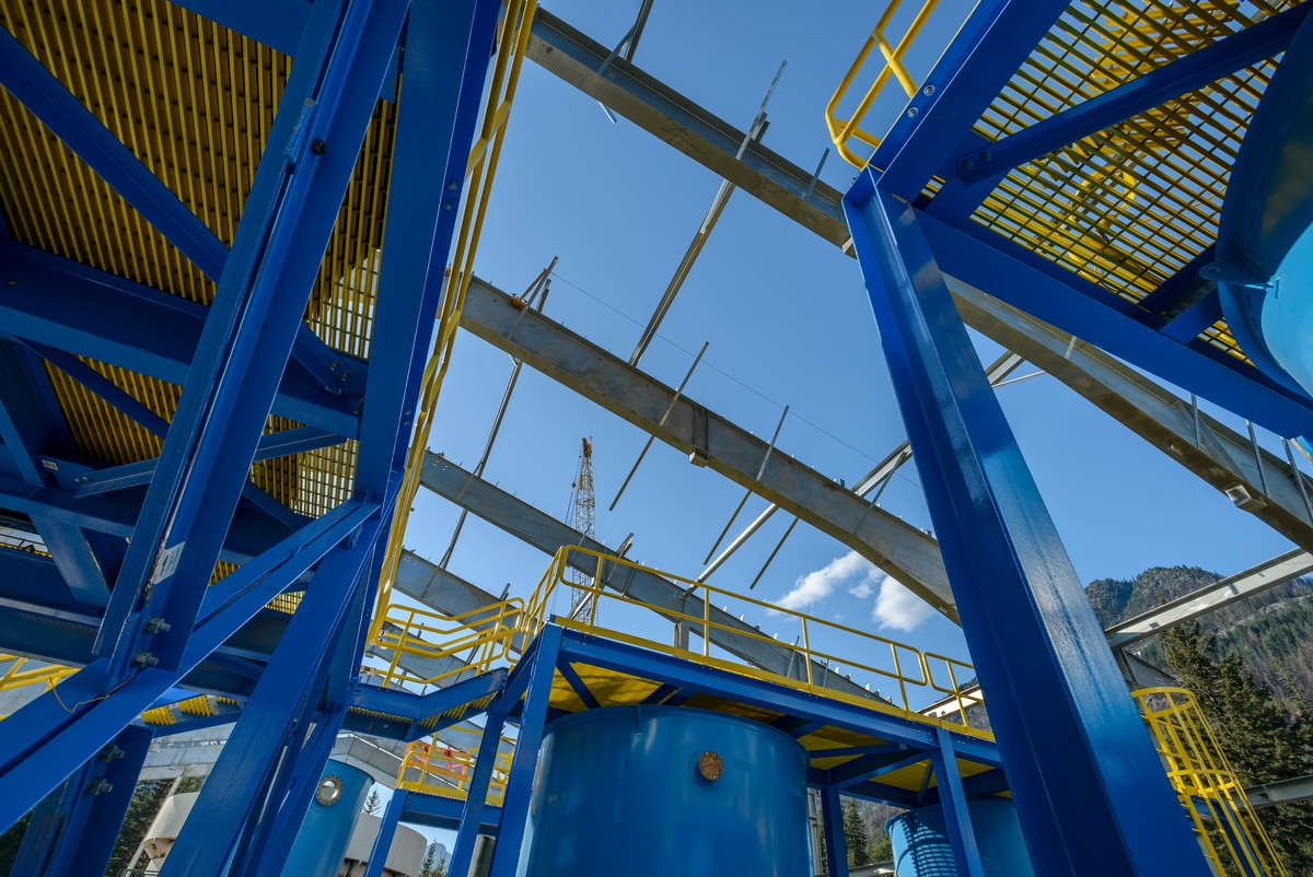 Looking up through blue steel structure with crane peeking through