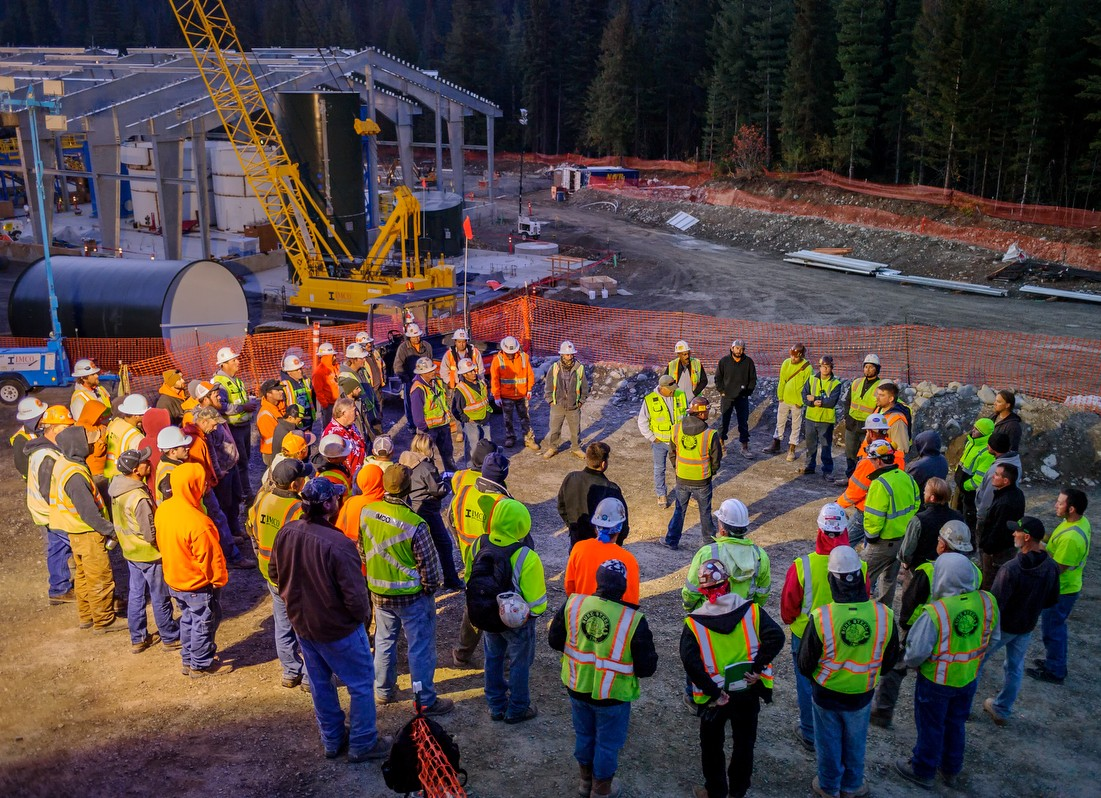 Group of IMCO construction workers circled together, meeting at sunrise