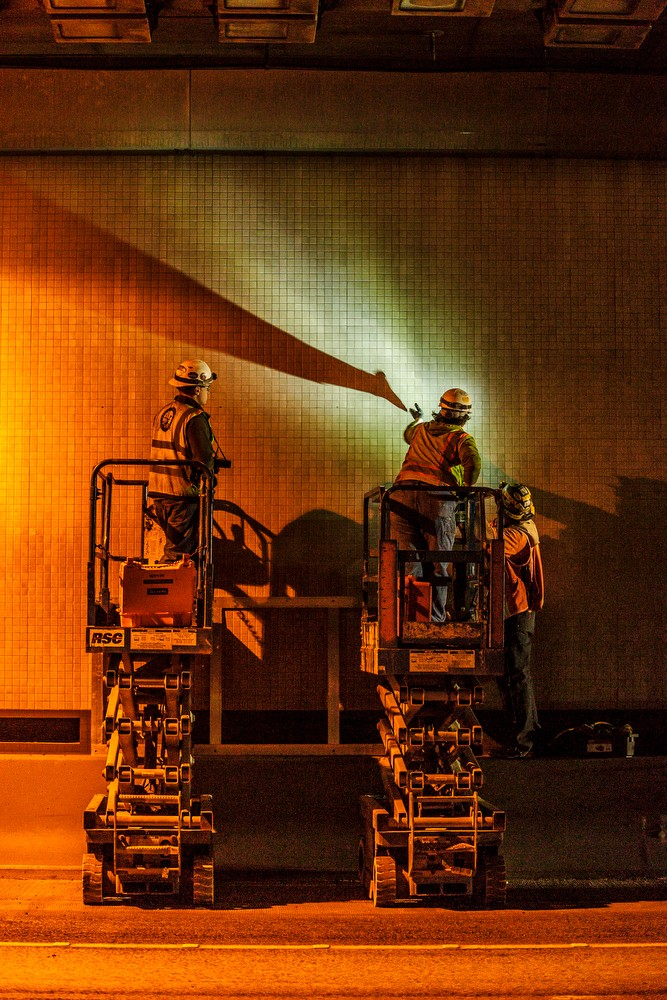 Two men working on lift inside tunnel