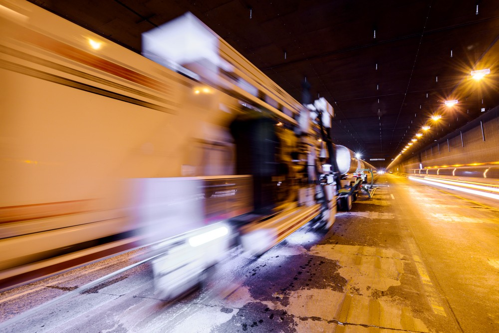 Blurred construction vehicle on a raodway at night with dramatic lighting