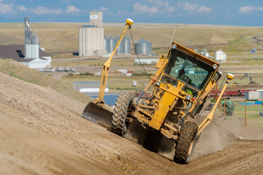 yellow grader with GPS gear and red train and industrial plant in background