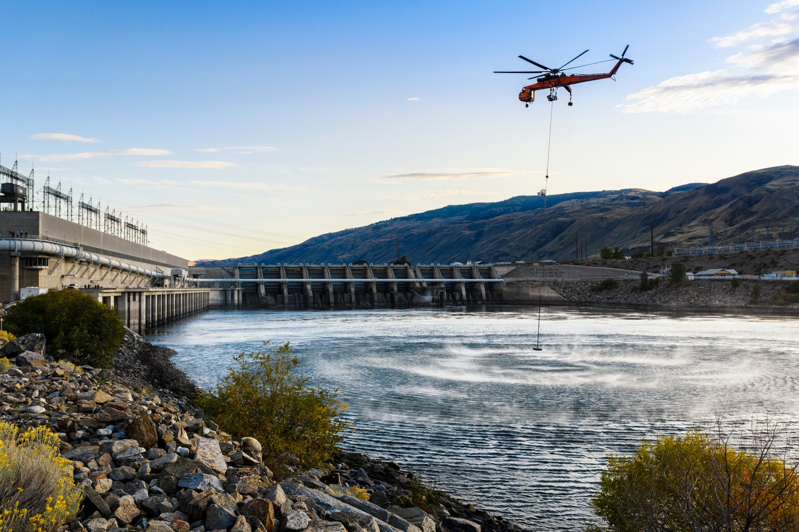 helicopter flying over river and dam facility