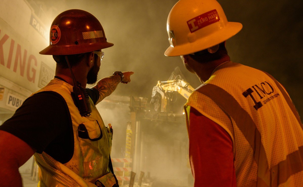Night work with two workers looking at construction site with bridge in background