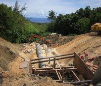 Guam valley construction site with pipes and excavators