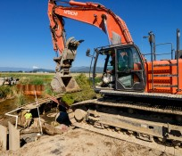 backhoe at work with operator and two men working along a dike with sheet pile in background