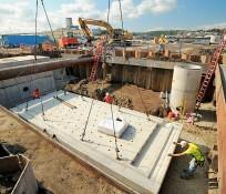 crane lowering platform into hole near harbor construction site