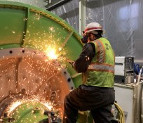 IMCO craft worker welding a turbine inside of a powerhouse