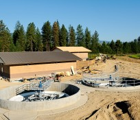 concrete process basins and wastewater treatment facility buildings with trees