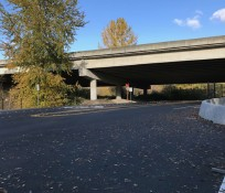 newly paved intersection under overpass with green bree in background and middle ground, blue sky